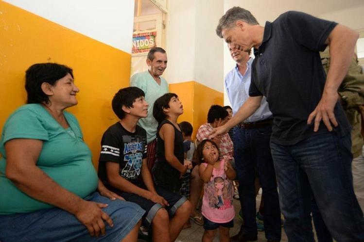 Mauricio Macri (der.) presidente de Argentina, durante una visita a víctimas d las recientes inundaciones en ese país. (Foto Prensa Libre: EFE).