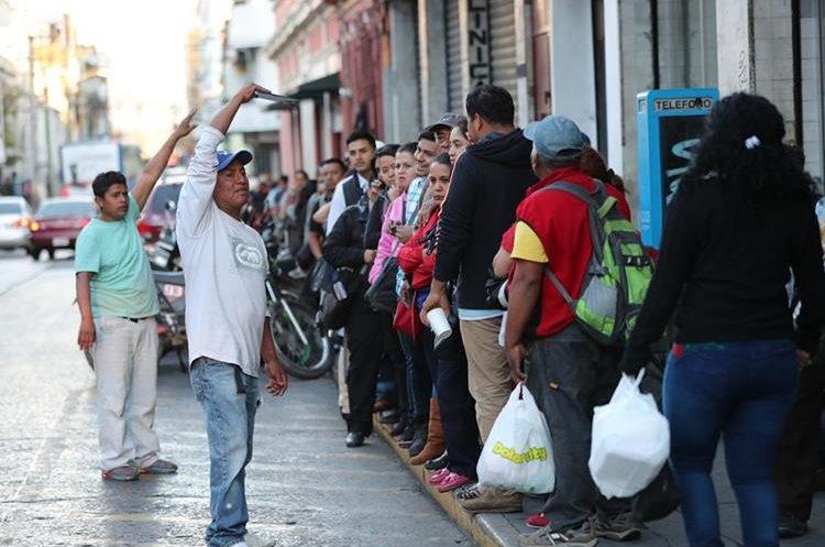 Usuarios hacen fila para abordar microbuses en la 17 calle y 6a. avenida, zona 1. (Foto Prensa Libre: Érick Ávila).