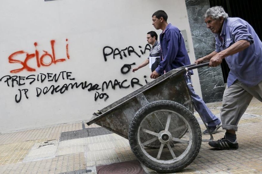 Hombres caminan frente a un mural que invita a votar por el oficialista Daniel Scioli. (Foto Prensa Libre: EFE).