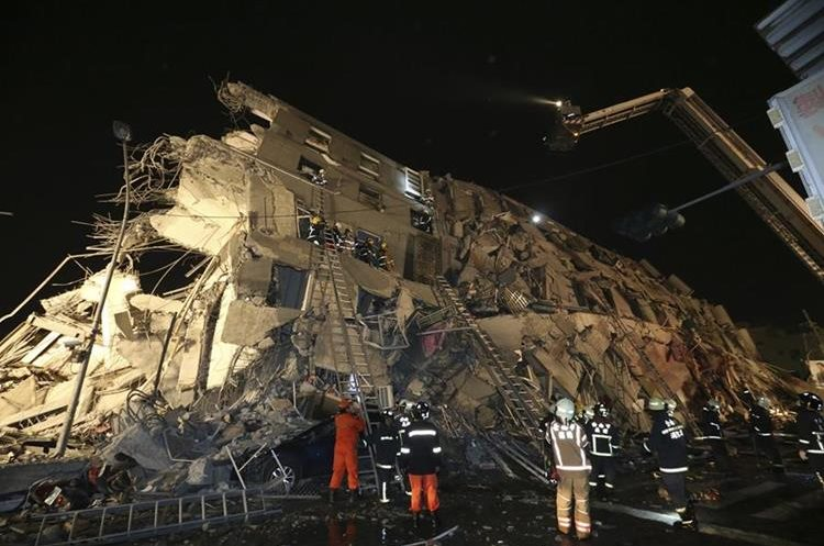 Rescue workers search a toppled building after an earthquake in Tainan, Taiwan, Saturday, Feb. 6, 2016. A 6.4-magnitude earthquake struck southern Taiwan early Saturday, toppling at least one high-rise residential building and trapping people inside. Firefighters rushed to pull out survivors. (AP Photo) TAIWAN OUT