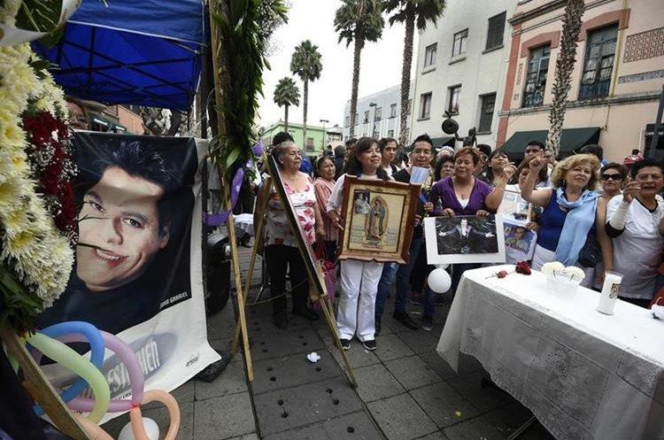 Seguidores cargan imágenes religiosas y del artista durante el homenaje (AFP).