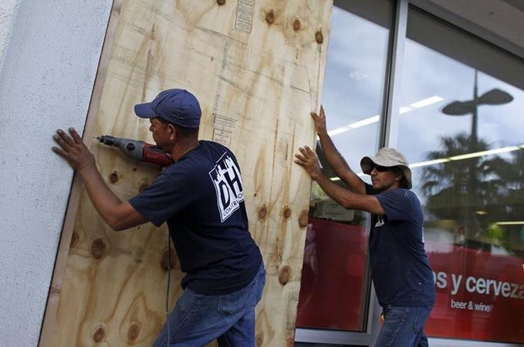 People board up windows of a business in preparation for the anticipated arrival of Hurricane Maria in San Juan, Puerto Rico on September 18, 2017. Hurricane Maria has grown into a maximum-strength Category Five storm, US forecasters said Monday, as it was bearing down on the Caribbean island of Dominica. / AFP PHOTO / Ricardo ARDUENGO