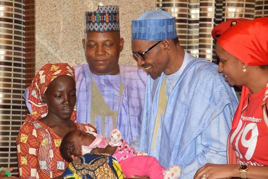 El presidente de Nigeria, Muhammadu Buhari (con lentes), recibe a Amina Ali, una de las jóvenes que había sido secuestrada por Boko Haram. (Foto Prensa Libre: AP).