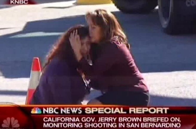 Two women comfort each other near the scene of a shooting outside a Southern California social services center in San Bernardino, Calif., where one or more gunmen opened fire, shooting multiple people on Wednesday, Dec. 2, 2015. (KNBC via AP) TV OUT