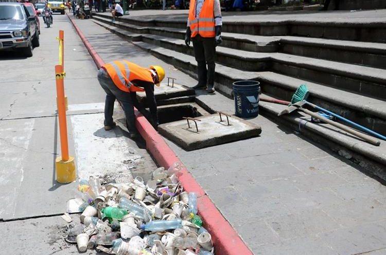 Cuadrillas hacen tareas de limpieza en los tragantes del Centro Histórico de Xelajú. (Foto Prensa Libre: Carlos Ventura)