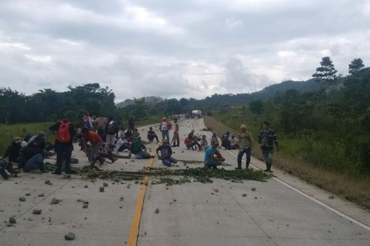 Invasores bloquean la ruta hacia Río Dulce, Lívingston, para evitar ser desalojados. (Foto Prensa Libre).