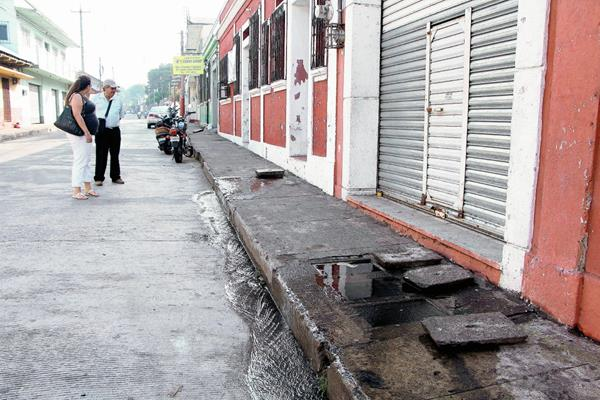 Vecinos verifican  las cajas de cemento en  donde estaban ubicados los medidores de agua. (Foto Prensa Libre: Rolando Miranda)