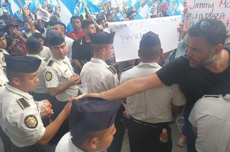 Manifestantes en la Plaza de la Constitución regalan champurradas a los agentes.