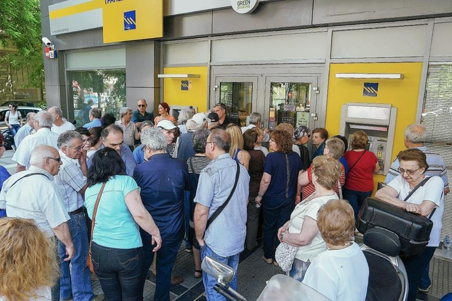 Un grupo de pensionistas hacen cola para retirar dinero en una sucursal bancaria. (Foto Prensa Libre:EFE).