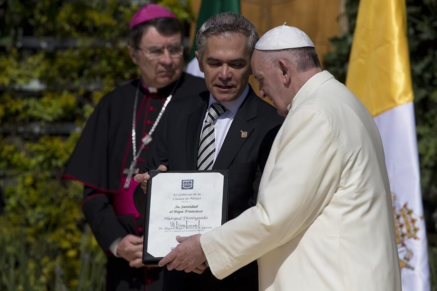 El Papa (d), recibe un reconocimiento como visitante distinguido de parte del alcalde de la ciudad de México, Miguel Ángel Mancera (i) en las puertas de la catedral. (Foto Prensa Libre: AP).