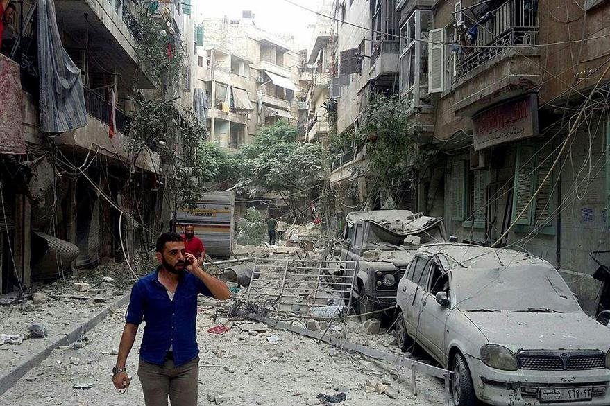 Un hombre camina por una de las calles devastadas de Alepo. El conflicto en Siria ha causado la muerte de más de 250 mil personas. (Foto Prensa Libre: EFE).