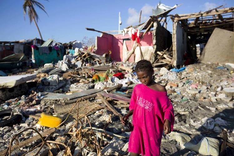 Una niña camina entre los escombros en Haití, luego del paso del devastador huracán Matthew en octubre del 2016. (Foto Prensa Libre: AP).