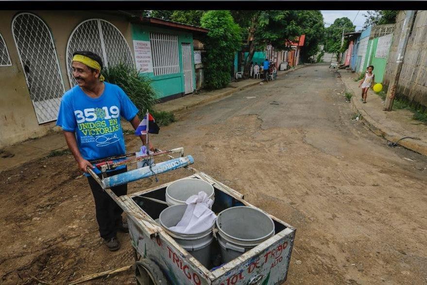 Un vendedor de atol de trigo camina por el barrio Villa Venezuela, en Managua.(AFP).