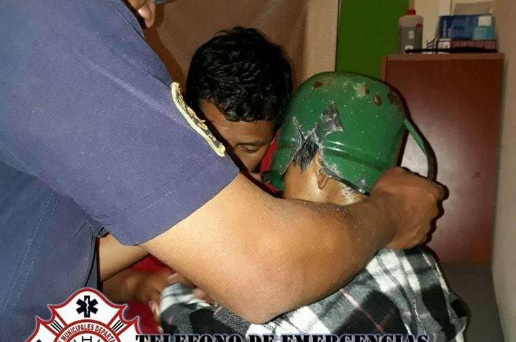 Bombero auxilia al menor para sacar su cabeza del pichel. (Foto Prensa Libre: CBMD)