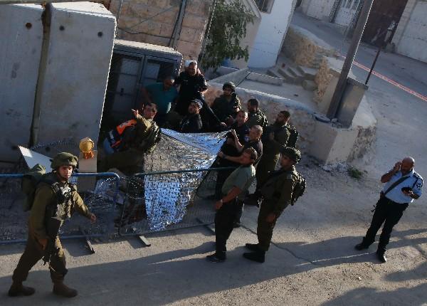 Soldados israelíes cubren el cuerpo de un palestino que murió tras atacar a uno de ellos. (AFP)