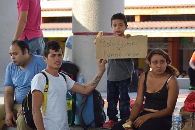 Una familias que acompaña el viacrucis del migrante muestra un rótulo que pide un futuro mejor. (Foto Prensa Libre: EFE)