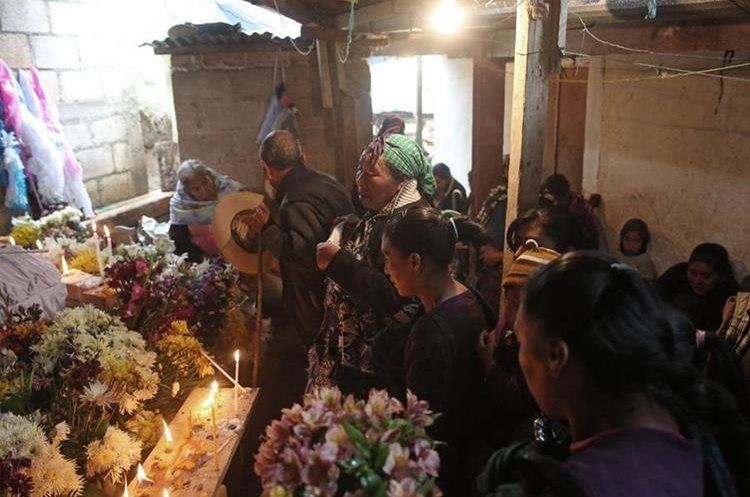 Familiares oran frente a los féretros de Aura Lorena y sus cuatro hijos, María Lorena, Elvira Vicenta, Fernanda Noemí y Alicio. (Foto Prensa Libre: EFE)