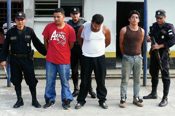 Los capturados en Santo Tomás de Castilla, Puerto Barrios, Izabal, son custodiados por agentes de la PNC. (Foto Prensa Libre: Edwin Perdomo)