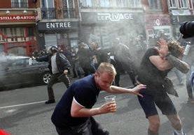 La policía tuvo que intervenir con gases lacrimógenos para evitar más actos violentos. (Foto Prensa Libre: AP)