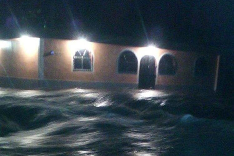Una de las calles inundadas en la aldea Milagro, Masagua, Escuintla. (Foto Prensa Libre: Conred)