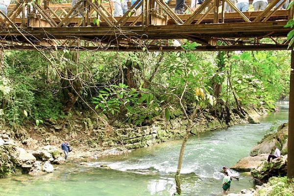 Pobladores de  Raxruhá y Fray Bartolomé de las Casas, Alta Verapaz, cruzan el río San Simón a pie, por bloqueo de puente. (Foto Prensa Libre: Facebook)