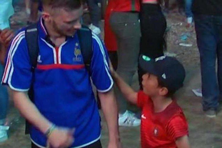 Un pequeño seguidor portugués consuela a un francés tras la derrota de la final. (Foto Redes Sociales).