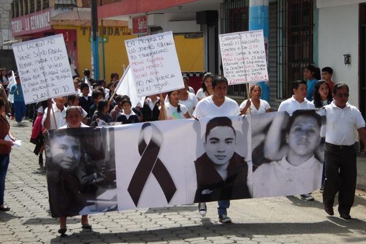 Pobladores portan manta con el rostro de los tres jóvenes ultimados recientemente en El Tejar. (Foto Prensa Libre: José Rosales).