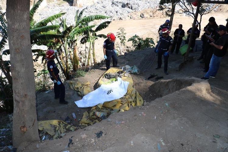 Socorristas rescatan el cuerpo de un PMT desaparecido en abril pasado en un deslizamiento en el relleno sanitaro. (Foto Prensa Libre: Estuardo Paredes)
