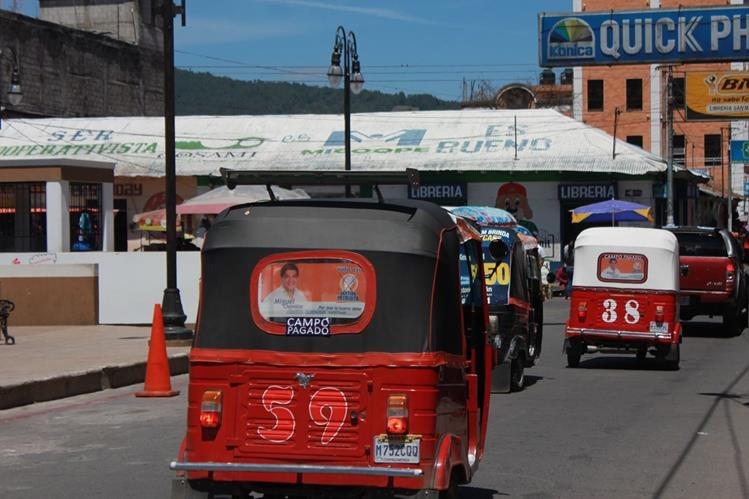 Unidades colectivas circulan en el parque central de Totonicapán con propaganda de Miguel Chavaloc, alcalde de la cabecera, quien busca la reelección. (Foto Prensa Libre: Lucero Sapalú)