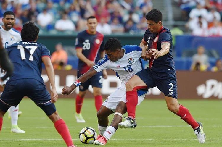 Miguel Camargo intenta controlar la pelota mientras que Johnny Acosta lo presiona. (Foto Prensa Libre: AFP)