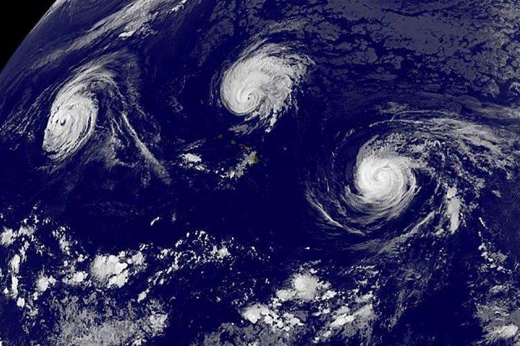 La imagen de la NASA muestra tres tormentas simultáneas en septiembre de este año. (Foto Prensa Libre: AFP).