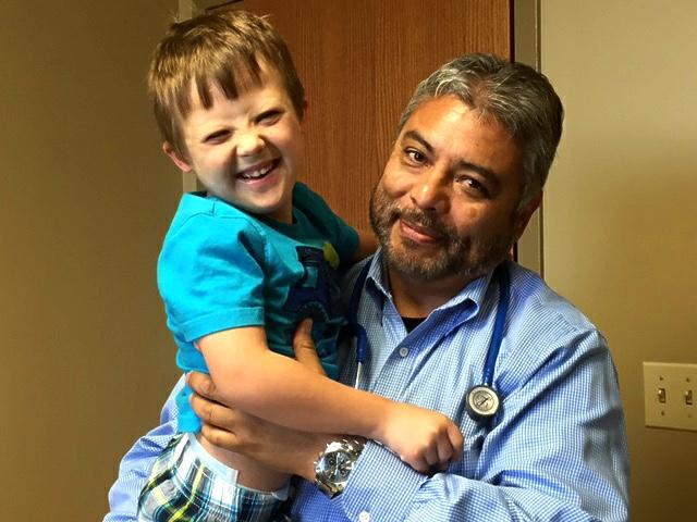 El genetista y pediatra guatemalteco, reconocido especialista en defectos congénitos en EE. UU., junto a uno de sus pequeños pacientes.