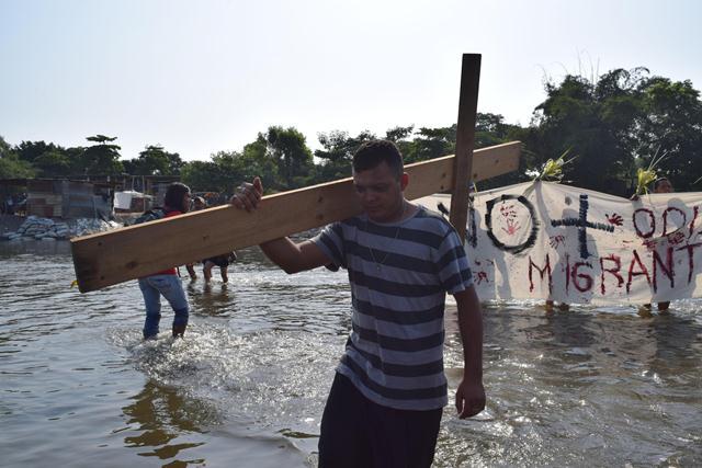 Migrante cruza un río con una cruz en el viacrucis del migrante. (Foto Prensa Libre: EFE)