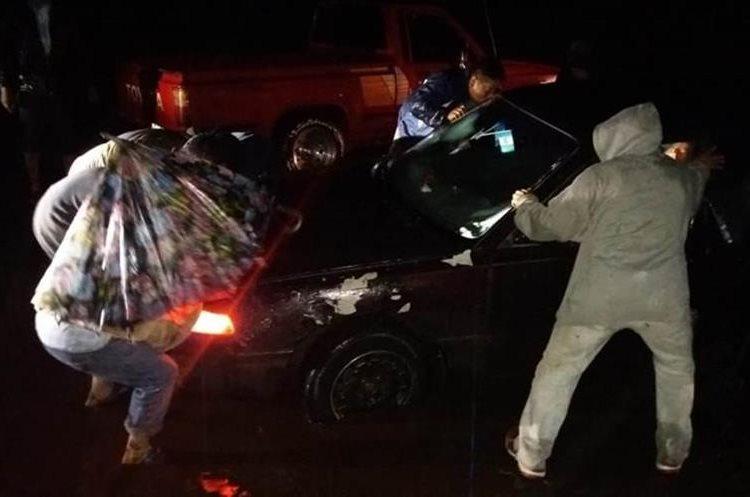 Pobladores y viajeros ayudaron para retirar al vehículo atascado en el lodo (Foto Prensa Libre: María Longo)