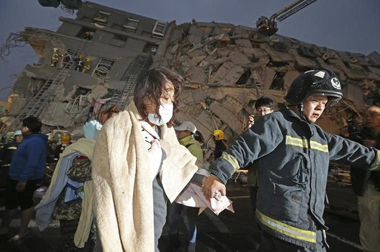 A woman is led by a rescue worker from the site of a toppled building after an earthquake in Tainan, Taiwan, Saturday, Feb. 6, 2016. A 6.4-magnitude earthquake struck southern Taiwan early Saturday, toppling at least one high-rise residential building and trapping people inside. Firefighters rushed to pull out survivors. (AP Photo) TAIWAN OUT