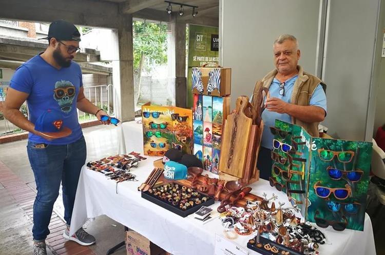 Ángel Moscoso – de playera azul- ordena los productos de su emprendimiento denominado Mayanché Guatemala. (Foto Prensa Libre: Oscar Fernando García).