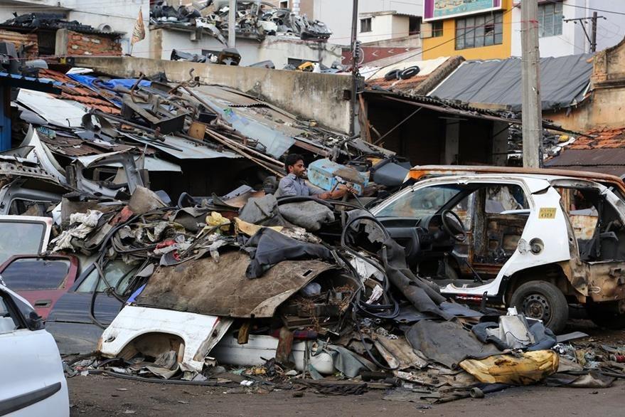 Un hombre trata de desmantelar un vehículo en un promontorio en Bangalore, India. (Foto Prensa Libre: AP).
