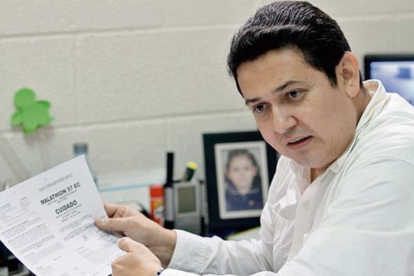 Luis Armando Menéndez, jefe del departamento de Registros de Insumos Agrícolas del Maga, muestra un modelo de registro de autorización. El experto refirió que los procesos duran hasta un año.