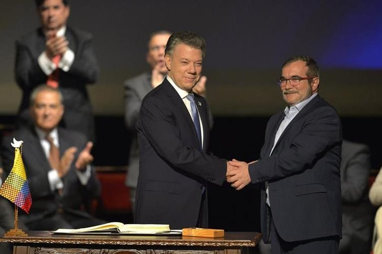 El presidente de Colombia, Juan Manuel Santos (izq.), saluda a Rodrigo Londoño, jefe máximo de las Farc, luego de la firma del nuevo acuerdo en Bogotá. (Foto Prensa Libre: AFP).