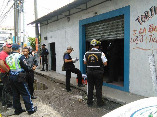 Policías inspeccionan la tortillería en la que fueron encontradas muertas dos mujeres, en Villa Nueva. (Foto Prensa Libre: Twitter)