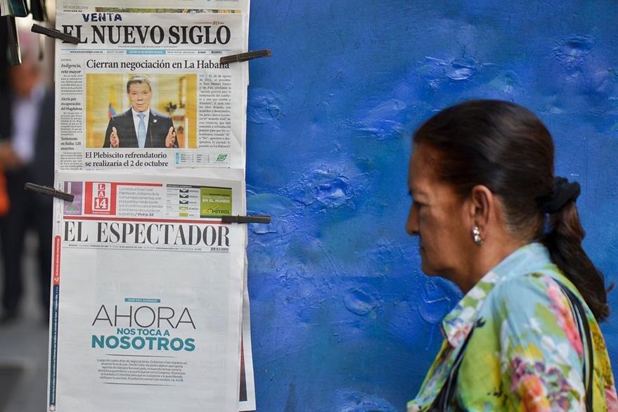 Una mujer camina frente a una venta de periódicos que destacan la histórica firma del acuerdo final de paz colombiano. (Foto Prensa Libre: AFP).