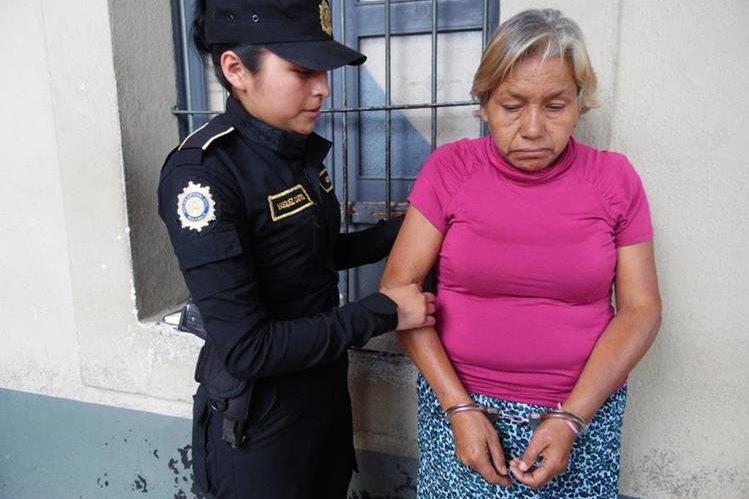 Clara Luz de León Álvarez es llevada por una agente de la PNC a la comisaría de Chimaltenango. (Foto Prensa Libre: José Rosales)