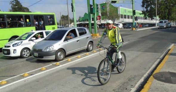 Un agente de Emetra maneja una bicicleta en la avenida Bolívar zona 8 capitalina, vistiendo el nuevo uniforme de color gris. (Foto Prensa Libre: Emetra)