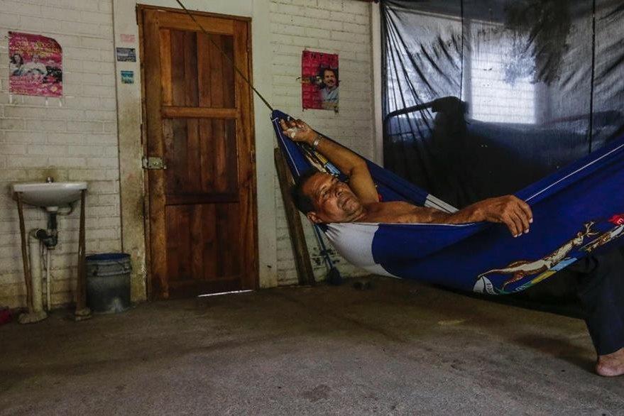 """Un hombre descansa en su casa de la """"Ciudadela héroes del Nemagón"""" en Managua. (AFP)."""