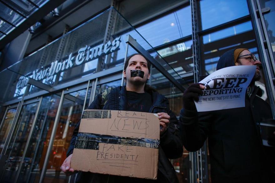 Un hombre se manifiesta frente a las instalaciones del The New York Times. (Foto Prensa Libre: AFP).