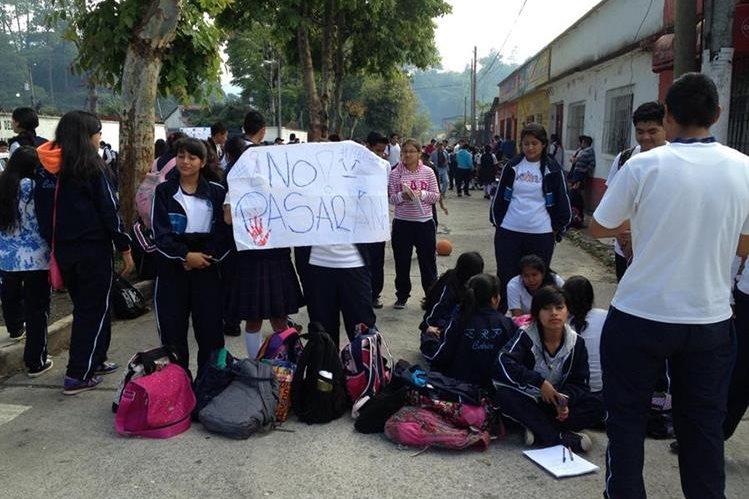 Estudiantes inconformes usaron carteles para dar a conocer el bloqueo de las calles aledañas al l instituto. (Foto Prensa Libre: Eduardo Sam)