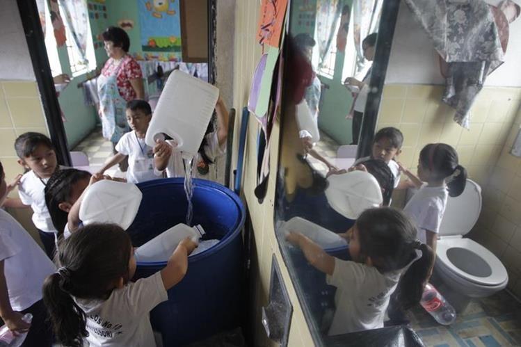 Niños llevan botes de agua a su escuela, donados por sus padres, para que los sanitarios e instalaciones se mantengan limpias e higiénicas. (Foto Prensa Libre: E. Barcian)
