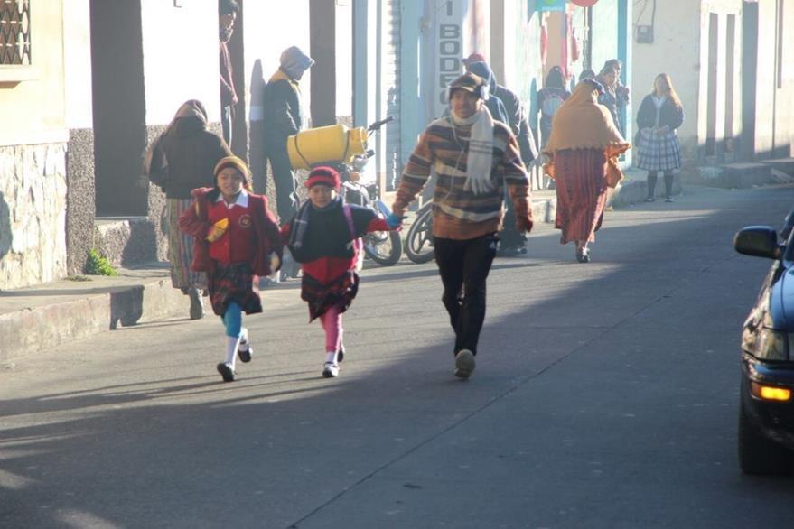 Niños de Totonicapán asisten abrigados a sus lugares de estudio, para evitar enfermedades respiratorias. (Foto Prensa Libre: Édgar Domínguez)