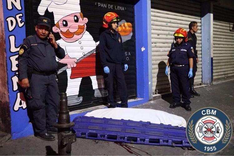 El cuerpo del agente de la PNC quedó en la banqueta, frente a una panadería, en Villalobos. (Foto Prensa Libre: Bomberos Municipales)