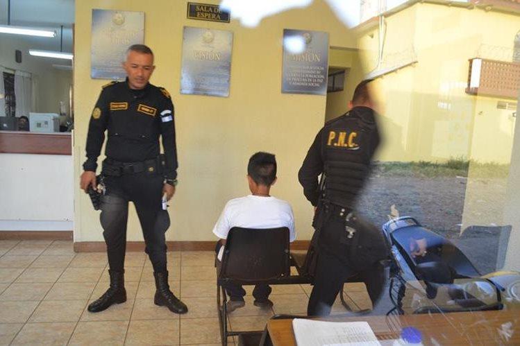 Agentes de la PNC custodian al adolescente detenido en Retalhuleu. (Foto Prensa Libre: Jorge Tizol).